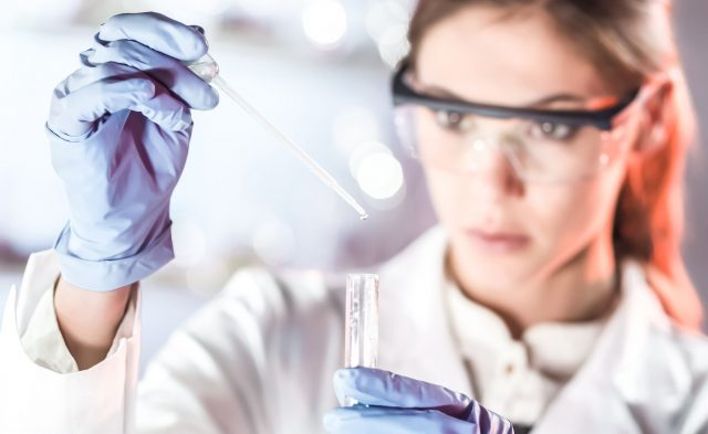 Woman wearing a white lab coat and PPE holding a pipette over a test tube