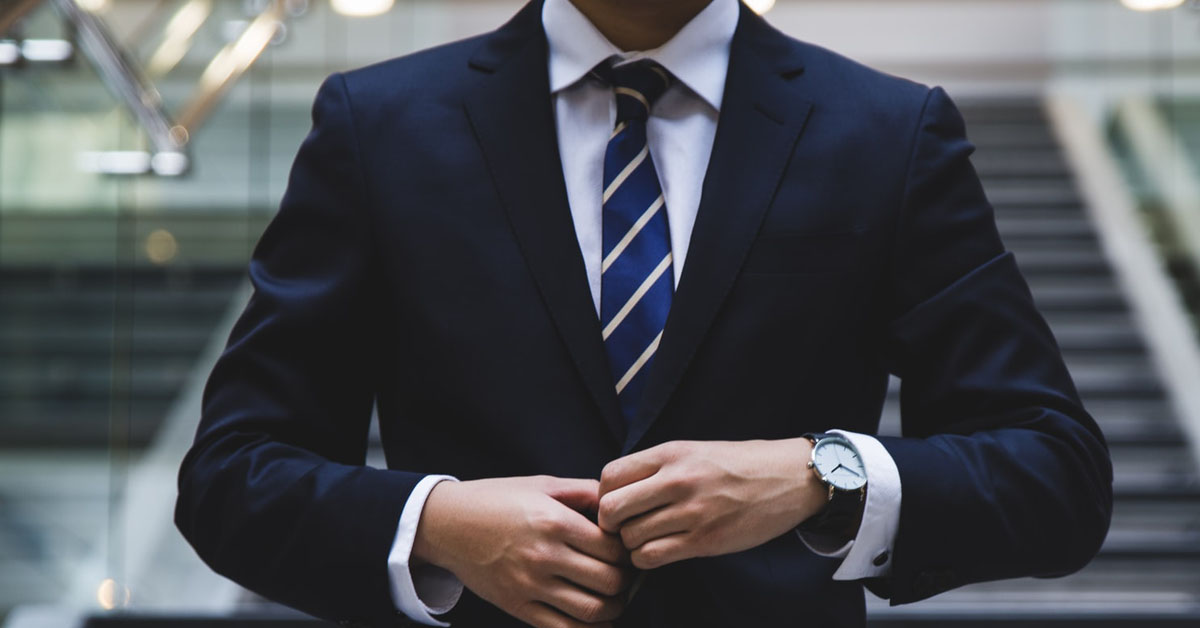 Businessman in navy suit with hands together closing his jacket button