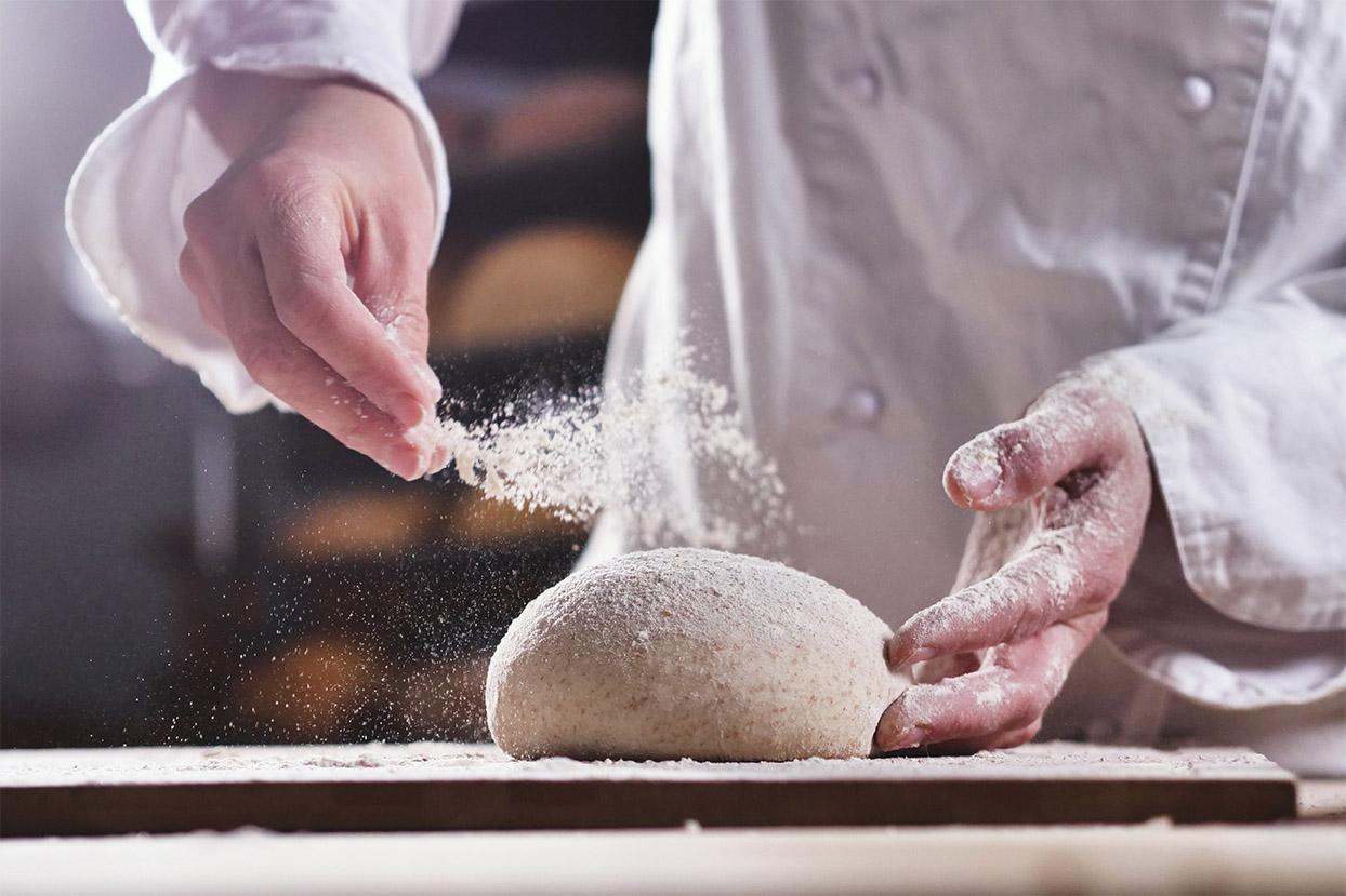 baker dusting some flour onto dough